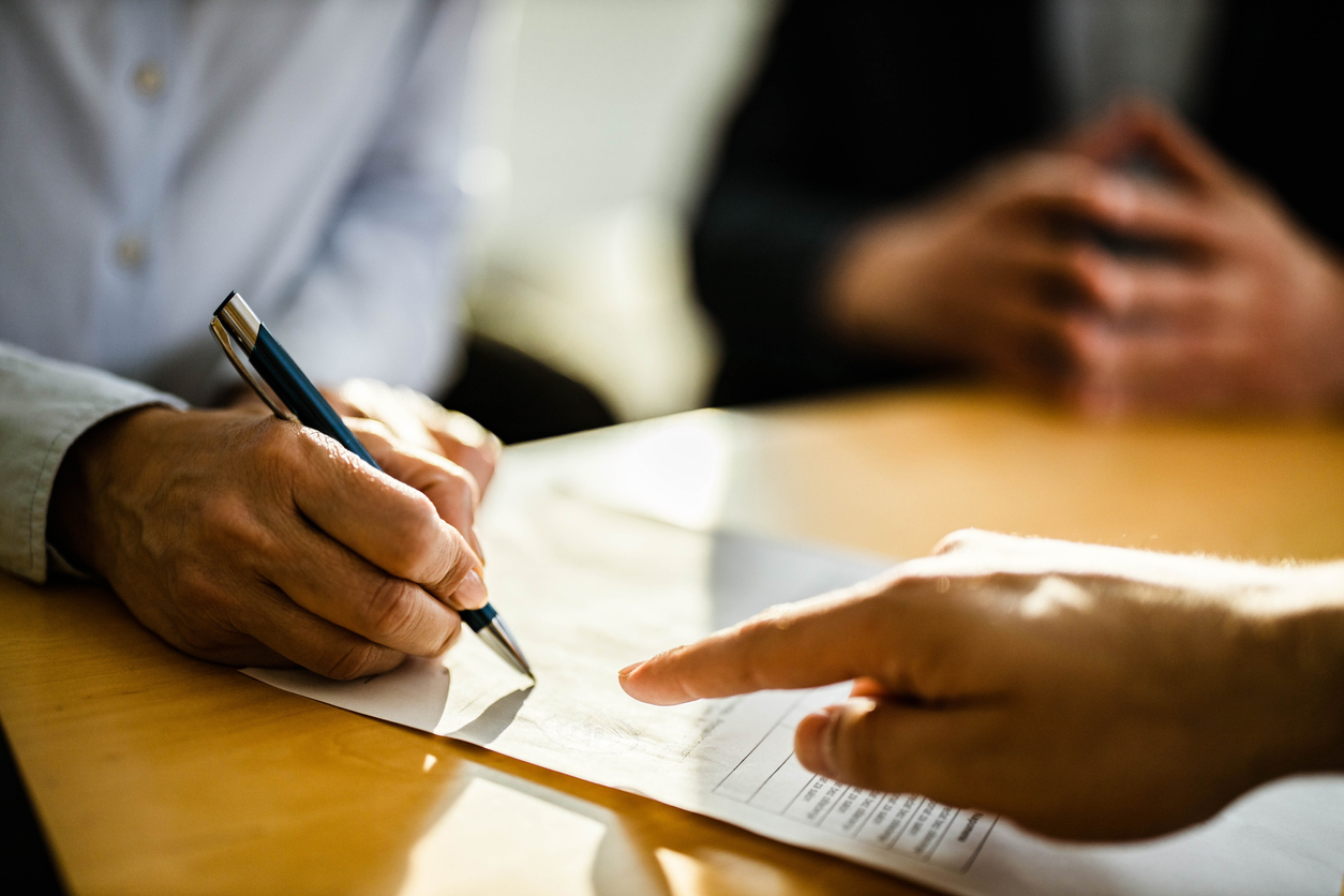 person-signing-contract contract-with-stamp-approval